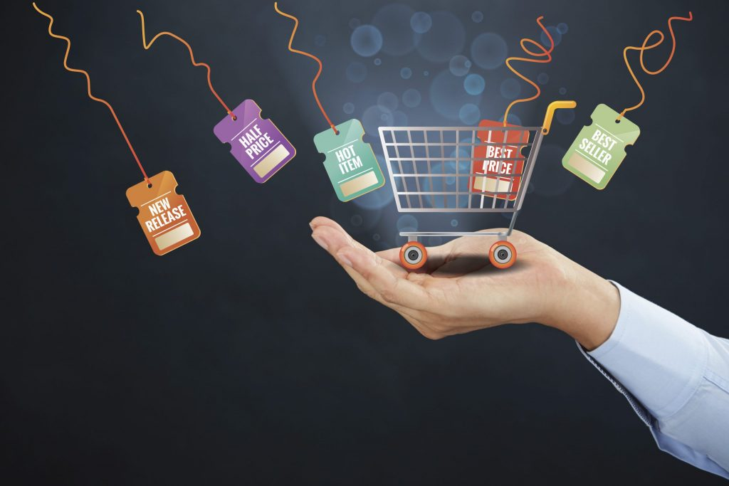 hand holding a little shopping cart representing ecommerce