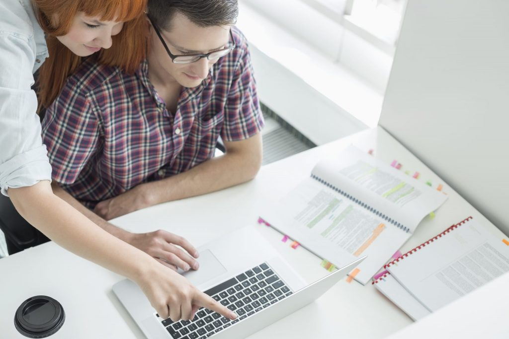 Business couple using laptop in creative office